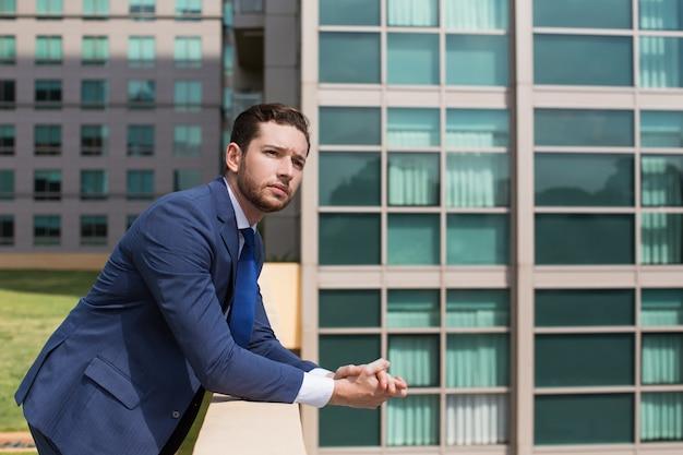 Zamyślony biznesmen leaning na balustrada na świeżym powietrzu