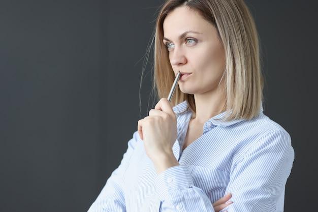 Zamyślony bizneswoman trzyma pióro i wygląda na odległość