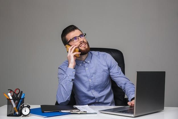 Zamyślony brodaty elegancki mężczyzna w okularach rozmawia przez smartfona siedząc przy stole w biurze