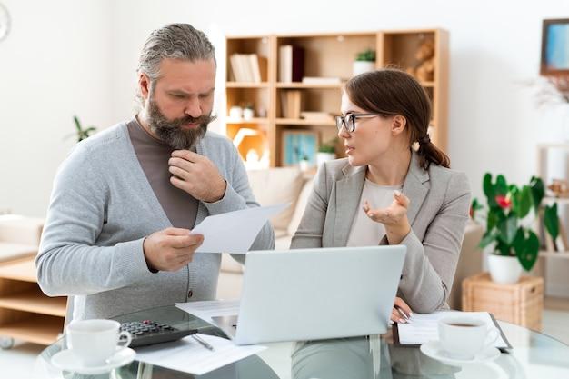 Zamyślony, brodaty mężczyzna o siwych włosach, patrząc przez papier, słuchając swojego agenta nieruchomości na spotkaniu