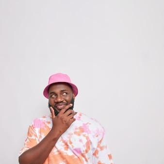 Zamyślony brodaty mężczyzna trzyma podbródek patrzy powyżej z podstępnym szczęśliwym wyrazem twarzy myśli o czymś, co ma na sobie kolorową koszulkę z różową panamą na białym tle nad białym bacground kopią miejsca powyżej