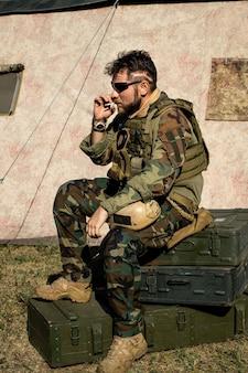 Zamyślony brodaty mężczyzna w kamuflażu siedzący na metalowych walizkach i palący papierosa na zewnątrz