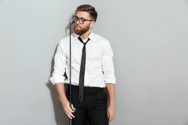 Zamyślony brodaty mężczyzna w okularach i ubrania biznesowe