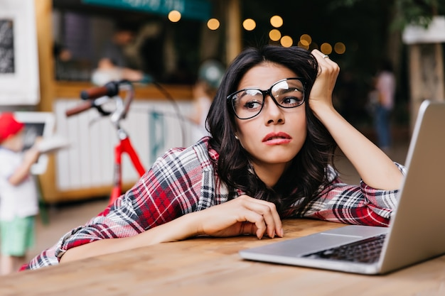 Zamyślony brunetka freelancer siedzi na zewnątrz i odwraca wzrok. portret zmęczona studentka zagraniczna w okularach przy użyciu komputera.