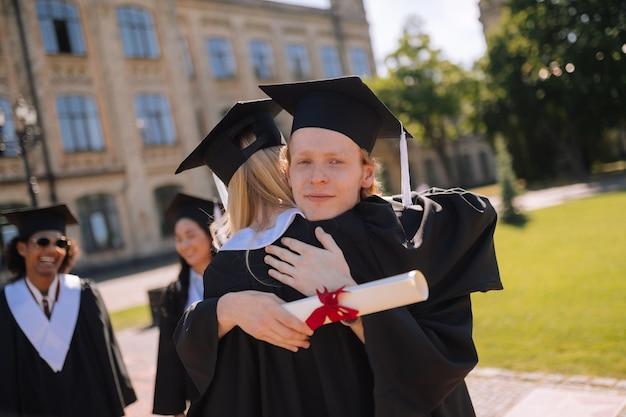 Zamyślony chłopiec przytulający swoją piękną koleżankę z grupy po ukończeniu studiów na kampusie