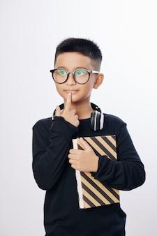 Zamyślony ciekawy chłopiec w okularach, trzymając książkę i dotykając wargi, na białym tle