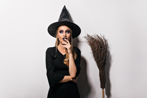Zamyślony czarodziejka pozowanie na białej ścianie. zmysłowa młoda czarownica w czarnym kapeluszu stojąca obok miotły.