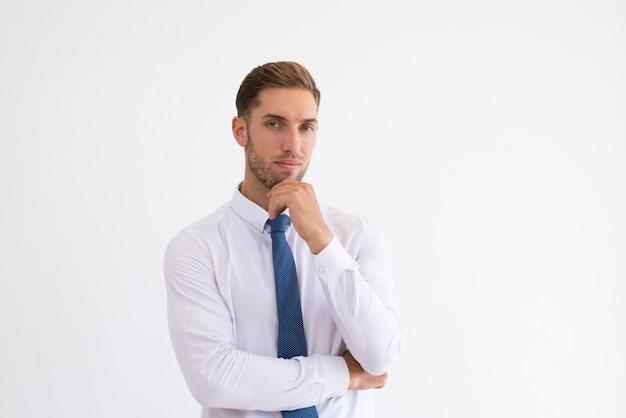 Zamyślony człowiek biznesu dotykając podbródek i patrząc na kamery
