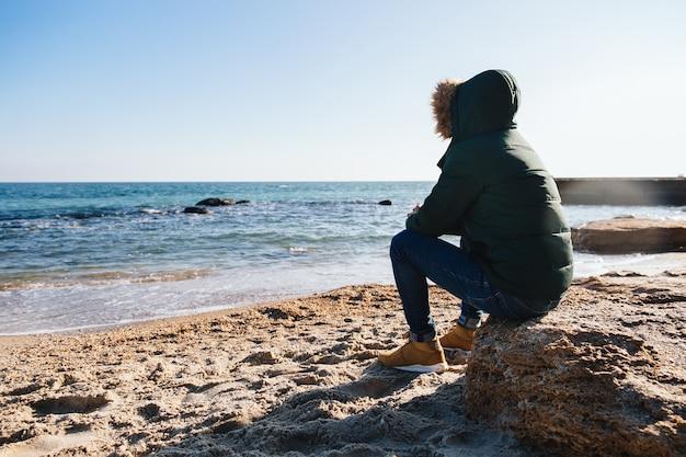 Zamyślony człowiek siedzi na kamieniu, patrząc na morze. ubrany w ciepłą kurtkę z kapturem.