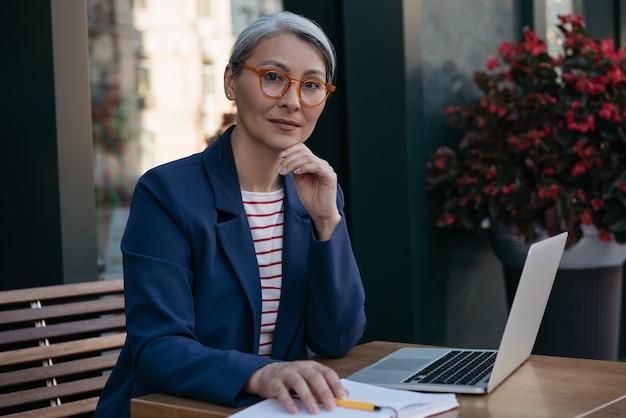 Zamyślony dojrzały biznes kobieta patrząc na kamery, siedząc w miejscu pracy
