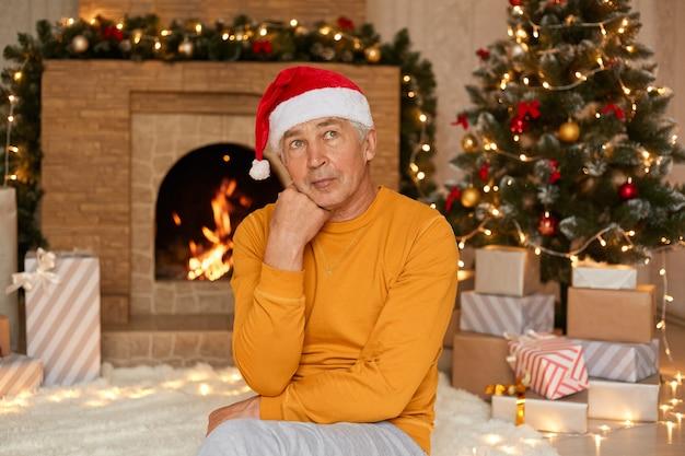 Zamyślony dojrzały mężczyzna siedzący w świątecznym pokoju z podbródkiem i odwracający wzrok, ubrany w swobodną żółtą koszulę i czapkę świętego mikołaja, pozujący przed kominkiem i choinką.
