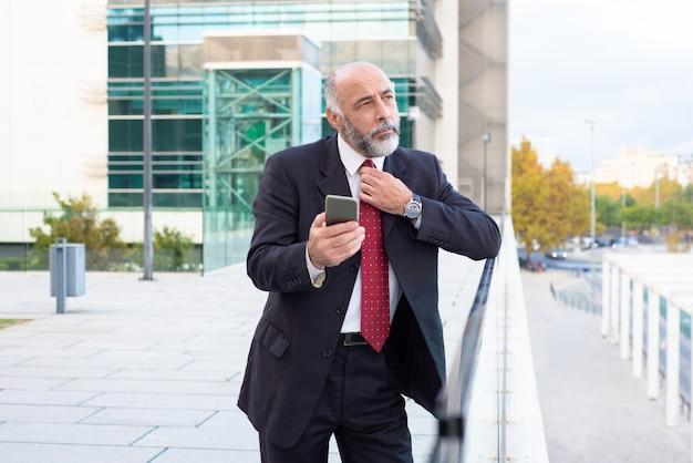 Zamyślony dojrzały wykonawca dostosowuje krawat i używa telefonu komórkowego
