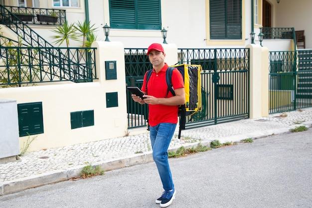 Zamyślony doręczyciel szuka adresu i trzyma tablet. profesjonalny kurier w czerwonej czapce i koszuli niosący żółtą torbę termiczną i dostarczający zamówienie. dostawa i koncepcja zakupów online