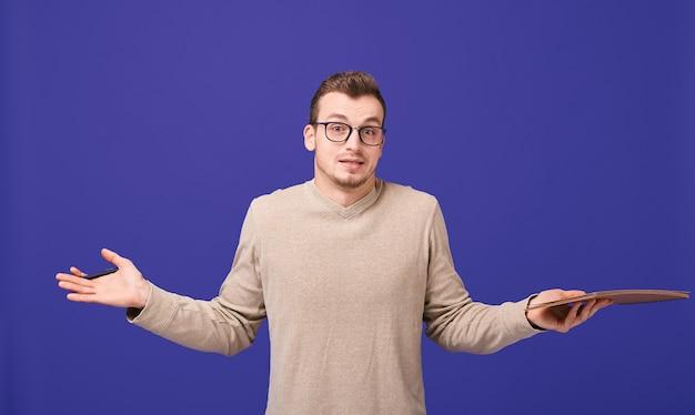 Zamyślony dziennikarz ze szkicem w swetrze i okularami rozkłada ręce na boki i wzrusza ramionami
