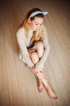 Zamyślony dziewczyna siedzi na podłodze ze skrzyżowanymi nogami. marzenia siedzą na podłodze