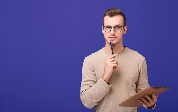 Zamyślony facet redactor stoi z brązowym papierowym notatnikiem w dłoni i czarnym długopisem w pobliżu twarzy