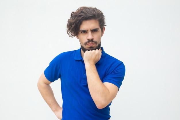 Zamyślony facet ściśle oparty na brodzie pod ręką