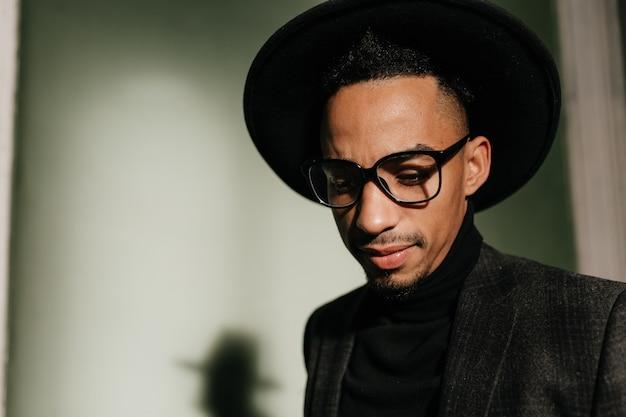 Zamyślony facet w okularach, patrząc w dół. kryty zdjęcie smutnego afrykańskiego mężczyzny w kapeluszu.