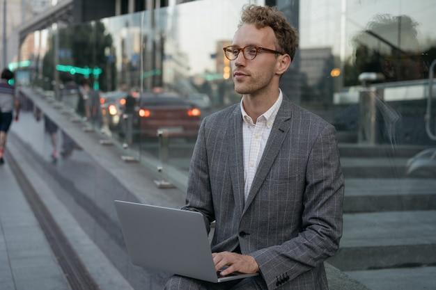 Zamyślony freelancer copywriter, piszący na laptopie, pracujący online, siedzący na miejskiej ulicy