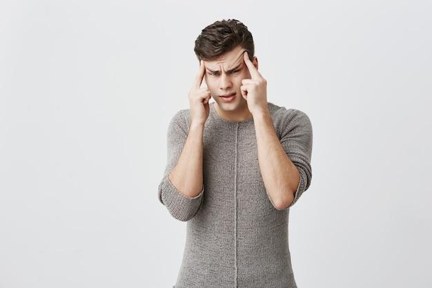 Zamyślony kaukaski przystojny mężczyzna ubrany w sweter, trzyma palce na skroniach, wygląda poważnie, zastanawia się, próbuje znaleźć odpowiednią decyzję w trudnej sytuacji. ludzie, młodzież, koncepcja stylu życia