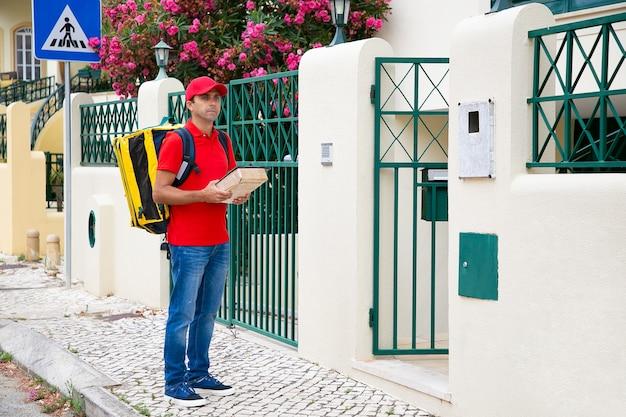 Zamyślony listonosz stojący na chodniku i trzymający paczkę. kaukaski kurier w średnim wieku czekający na klienta na zewnątrz, odwracający wzrok i niosący żółty plecak. usługa dostawy i koncepcja poczty