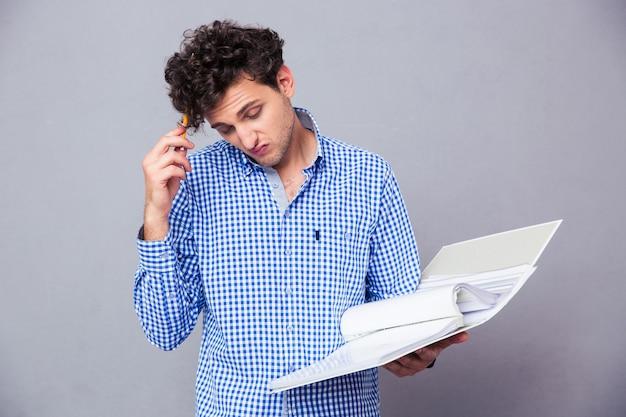 Zamyślony mężczyzna trzyma ołówek i folder z teczką