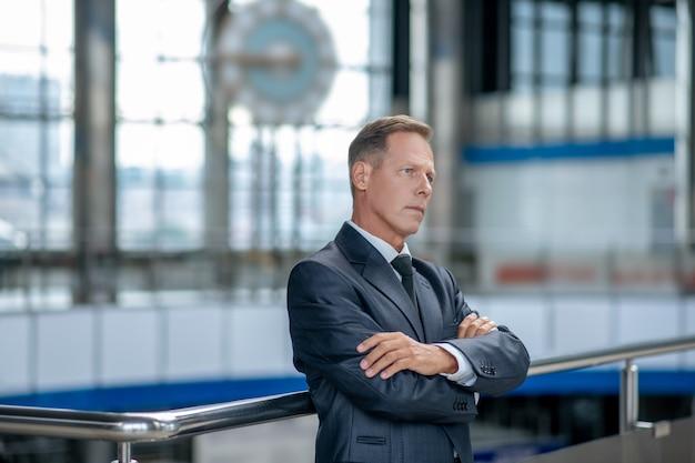 Zamyślony mężczyzna w garniturze czeka na lotnisku