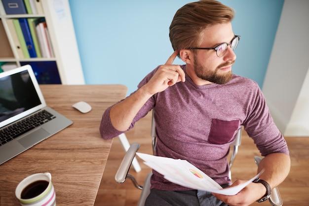 Zamyślony mężczyzna w swoim domowym biurze