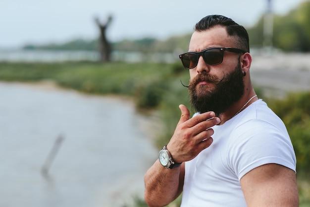 Zamyślony mężczyzna z brodą w plenerze