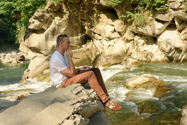 Zamyślony mężczyzna z notatnikiem siedzi na brzegu rzeki nad wodospadem