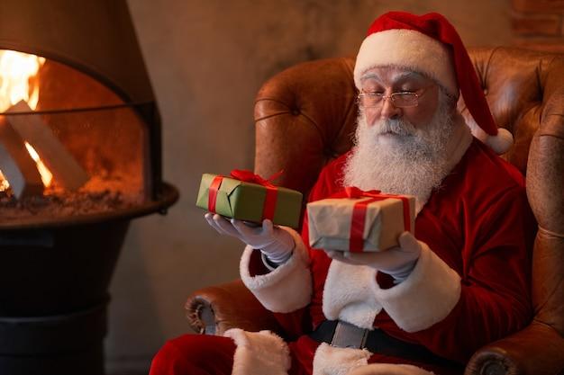 Zamyślony mikołaj siedzi w wygodnym fotelu przy kominku i porównuje świąteczne prezenty