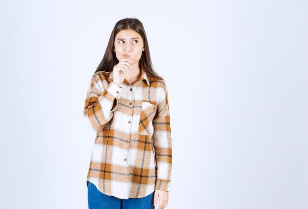 Zamyślony młoda dziewczyna model stojący i odwracający wzrok.
