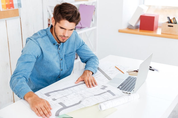 Zamyślony młody biznesmen patrząc na diagram siedząc przy biurku