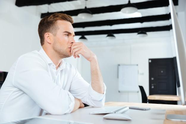 Zamyślony młody biznesmen pracujący z komputerem i myślący w miejscu pracy