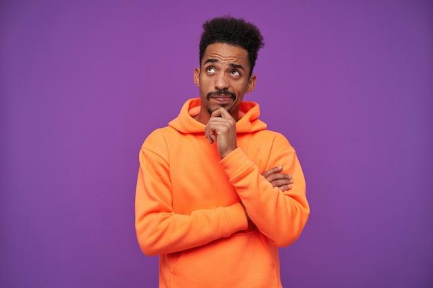 Zamyślony młody brązowooki brodaty mężczyzna o ciemnej skórze, trzymający brodę z uniesioną ręką i patrząc w górę w zamyśleniu, ubrany w pomarańczową bluzę z kapturem na fioletowo