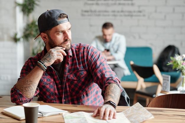 Zamyślony młody brodaty mężczyzna siedzi przy stole w kawiarni i odwraca wzrok, myśląc o nowej podróży