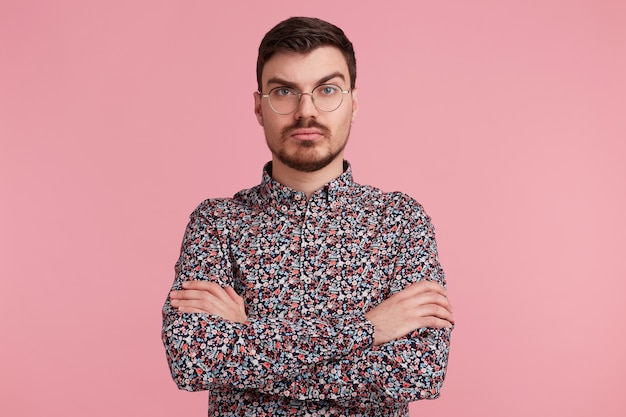 Zamyślony młody brodaty mężczyzna w okularach w kolorowej koszuli, myśląc o czymś, stojąc z rękami skrzyżowanymi z jedną uniesioną brwią pytający, z poważnym i zdziwionym wyrazem twarzy na różowej ścianie