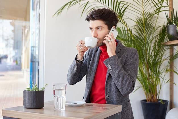 Zamyślony, młody, całkiem ciemnowłosy biznesmen pije kawę i dzwoni ze swojego smartfona, patrząc w zamyślenie przed siebie, pozując na tle kawiarni