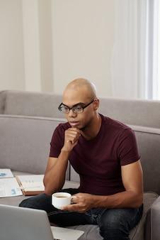 Zamyślony młody czarny przedsiębiorca pije kawę i ogląda prezentację na ekranie laptopa