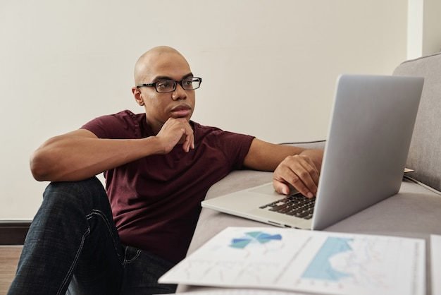 Zamyślony młody czarny przedsiębiorca w okularach siedzi na podłodze w domu i czyta raport lub artykuł na ekranie laptopa