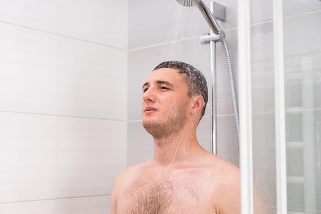 Zamyślony młody człowiek bierze prysznic i myśli o czymś, stojąc pod płynącą wodą w kabinie prysznicowej z przezroczystymi szklanymi drzwiami w łazience