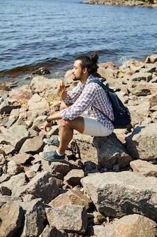 Zamyślony młody człowiek drogą morską