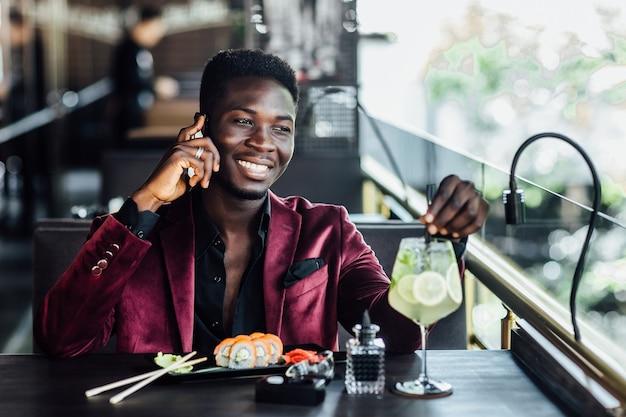 Zamyślony młody człowiek je sushi i rozmawia przez telefon na tarasie nowoczesnej restauracji.