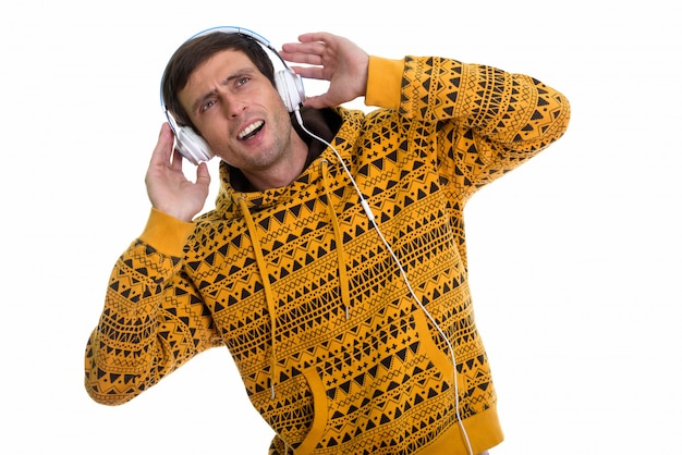 Zamyślony młody człowiek, słuchając muzyki i patrząc zszokowany, trzymając słuchawki