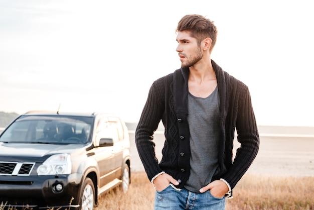 Zamyślony młody człowiek stojący na plaży z samochodem na tle