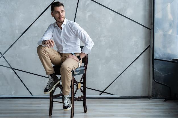Zamyślony młody człowiek w pełnym garniturze odwracający wzrok siedzący na stołku.