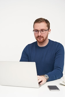 Zamyślony młody, dość brodaty jasnowłosy facet w okularach koncentruje się na swojej pracy, siedząc na białym tle, pisząc literę na klawiaturze