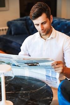 Zamyślony młody formalnie ubrany mężczyzna czyta gazetę