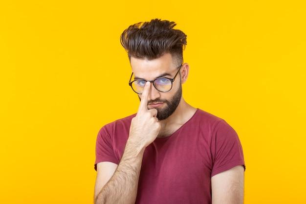 Zamyślony młody hipster mężczyzna z brodą, trzymając okulary, stojąc przed żółtą ścianą