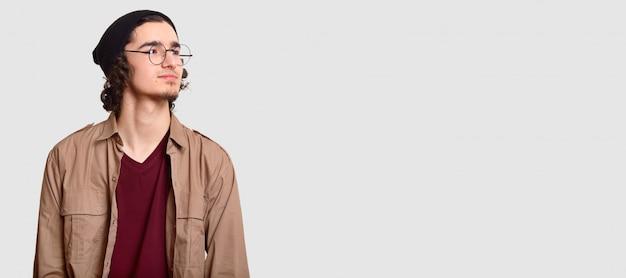 Zamyślony młody hipster wygląda z zamyśleniem na bok, nosi okrągłe okulary, codzienne ubrania, na białym tle z wolnym miejscem na treści reklamowe lub promocyjne